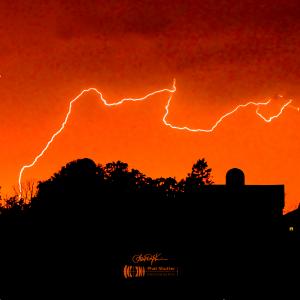 Photo of a lightning strike on a red sky