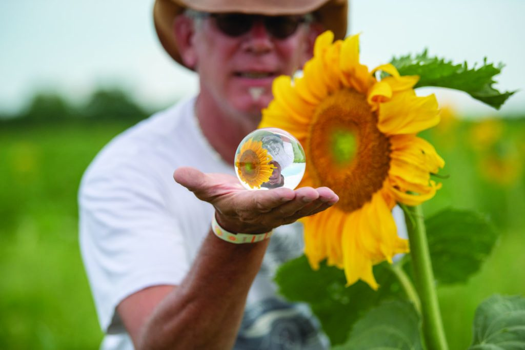 Picture of the artist holding a lensball in front of a sunflower
