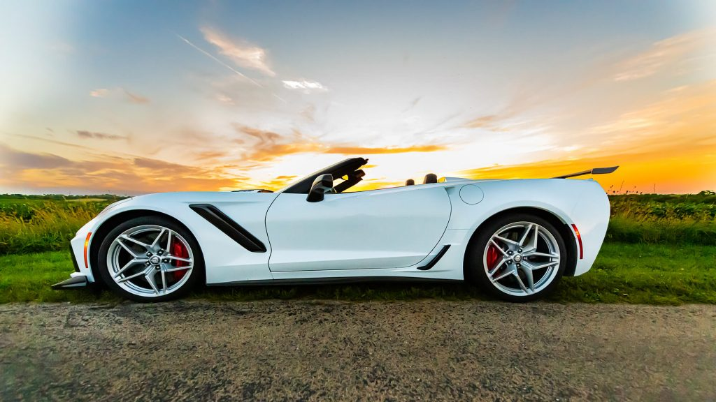 A side-shot of an Arctic White, convertible, 2019 Chevrolet Corvette ZR1 on a rural road at sunset